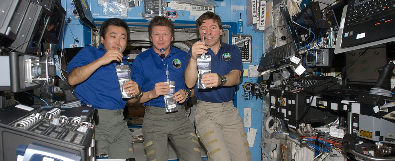 Astronauts showing how to drink liquids in space.