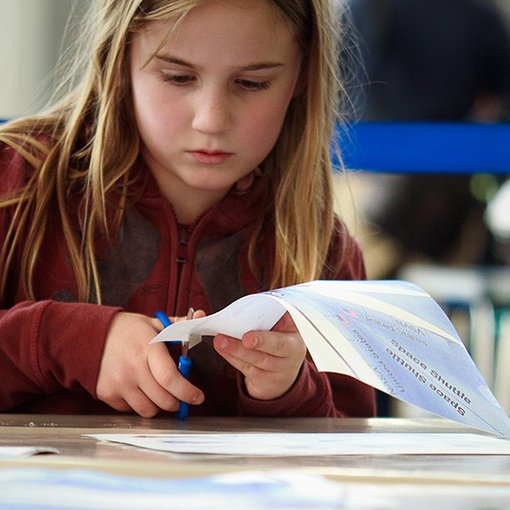 Girl making a mini space ship out of paper.