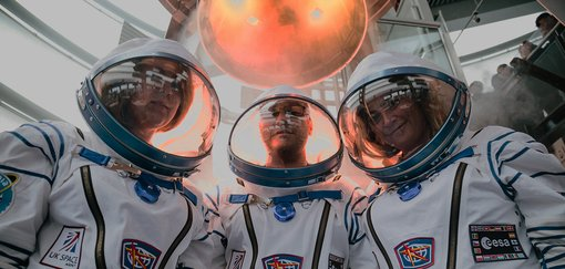 Three astronauts in space suits.