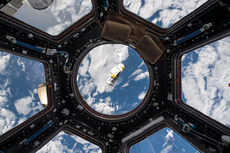 A lego astronaut in space and view of planet earth from the international space station.