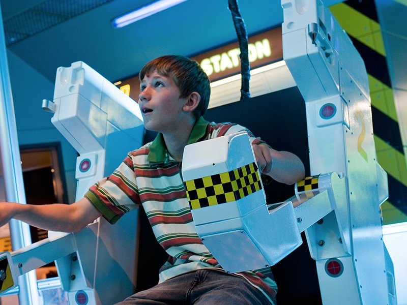 Boy testing a flight simulator at science centre.